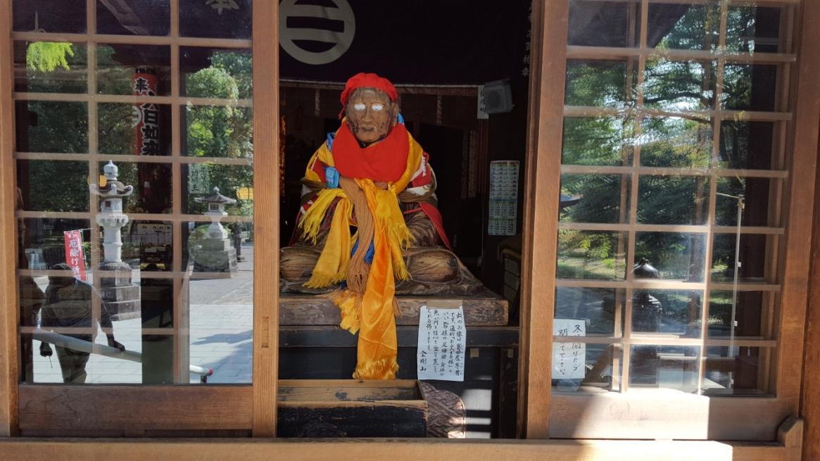 御堂の前には、いつの時代のものか分からないですが、気持ちの悪いミイラの様な像が祀られています。 この像は、釈迦の弟子の一人、「賓頭盧尊者(びんずるそんじゃ)」です。 信心深い方々には、「おびんづるさん」と親しまれてきた方で、中国、日本等のアジアでは尊者として祀られてきました。 日本では堂の前に置き、撫でると除病の功徳があるとされ、撫で仏の風習が広がったとされています。