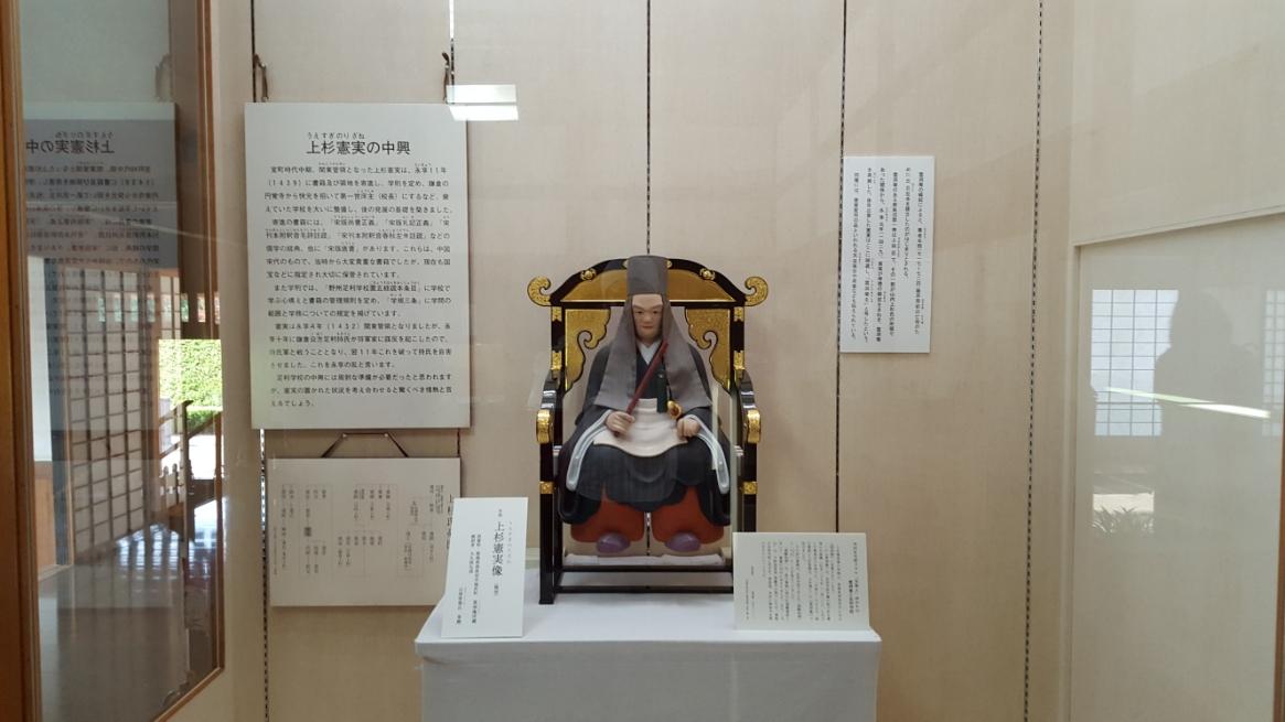 中に入ると「足利学校」への中興を齎した「上杉憲実」公の像が展示されていました。 ここに書かれた内容によると「足利学校」は、室町時代の前期には衰退していたが1432年に上杉憲実が足利の領主となり再興し、鎌倉円覚寺の僧快元を能化に招いたり蔵書の寄贈を行い再興しました。 能化とは今日の学校の校長先生にあたります。 江戸時代には、「庠主(しょうしゅ)」と呼ばれるようになりました。 その成果もあり北は奥羽、南は琉球の全国から来学に訪れました。 ここでの教育は上杉憲実が定めた3ヶ条の規定があり、「四書」、「六経」、「列子」、「荘子」、「史記」、「文選」のみと定められ、仏教の経典は寺院で学ぶべきとし、教員は禅僧の僧侶であるものの、教育内容から仏教色を排除した事が特徴であります。 教育の中心は儒学であり、快元が「易学」にも精通していた事から、易学を学びに訪れる者も多く「兵学」、「医学」等も学ぶ事が出来たとあります。