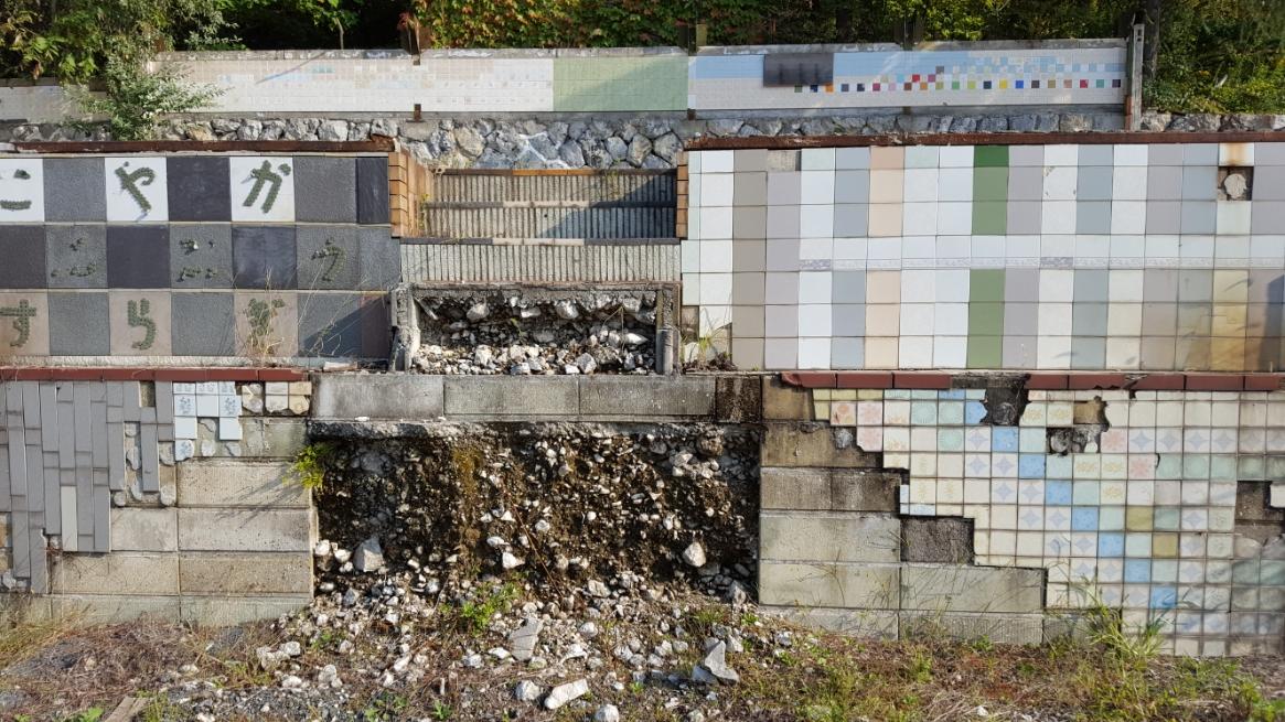 タイルが剥がれ崩壊しつつある土台の中から見える、コンクリートブロック。 さらにその中には不純物が大量に混じった土砂が見えます。 これは、産廃物で作られた建造物なのでしょうか?