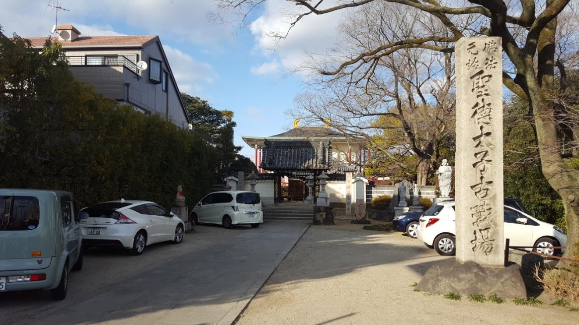 門前には、「聖徳太子古戦場」の石碑があり、奥に「大聖勝軍寺」が見える造りになっております。 ちなみに、写真には車が数台駐車されておりますが、本来は駐車場の無い寺院ですのでお立寄りの際は、付近の有料コインパーキングに駐車される事をおススメします。